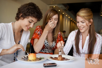 three women eating around a table