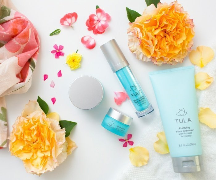 TULA skincare products flatlay with flowers
