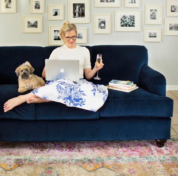 Ashley sitting on blue Society Social Velvet Couch