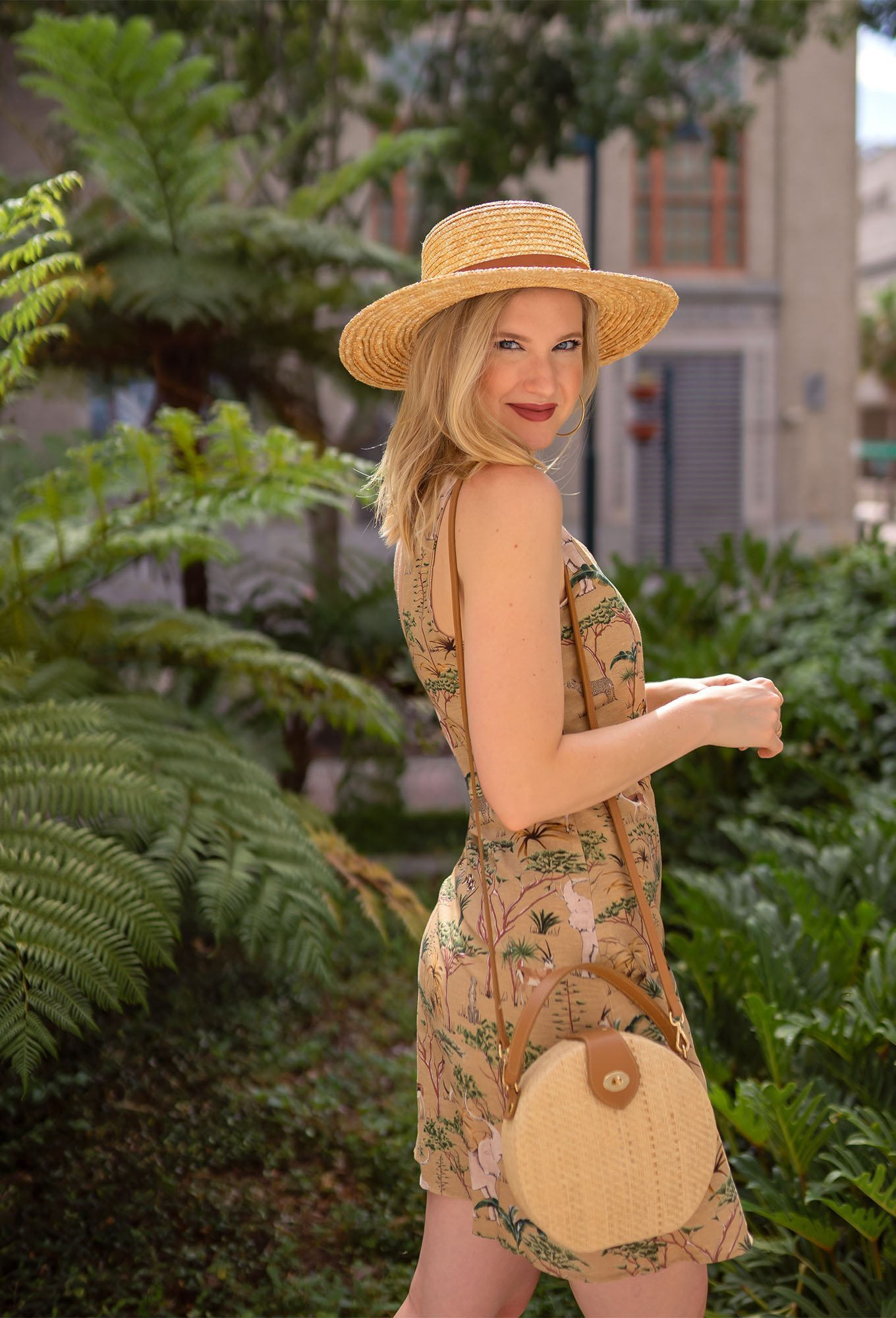 Ashley Brooke styles outfit with straw hat and animal print dress.