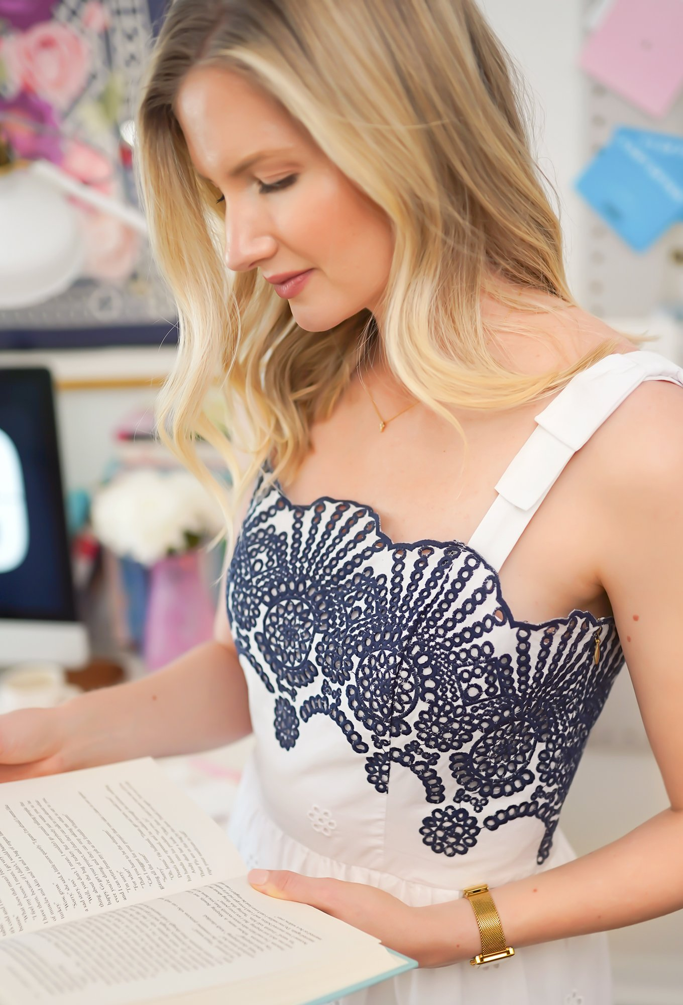 Ashley Brooke reading in blue and white embroidered dress