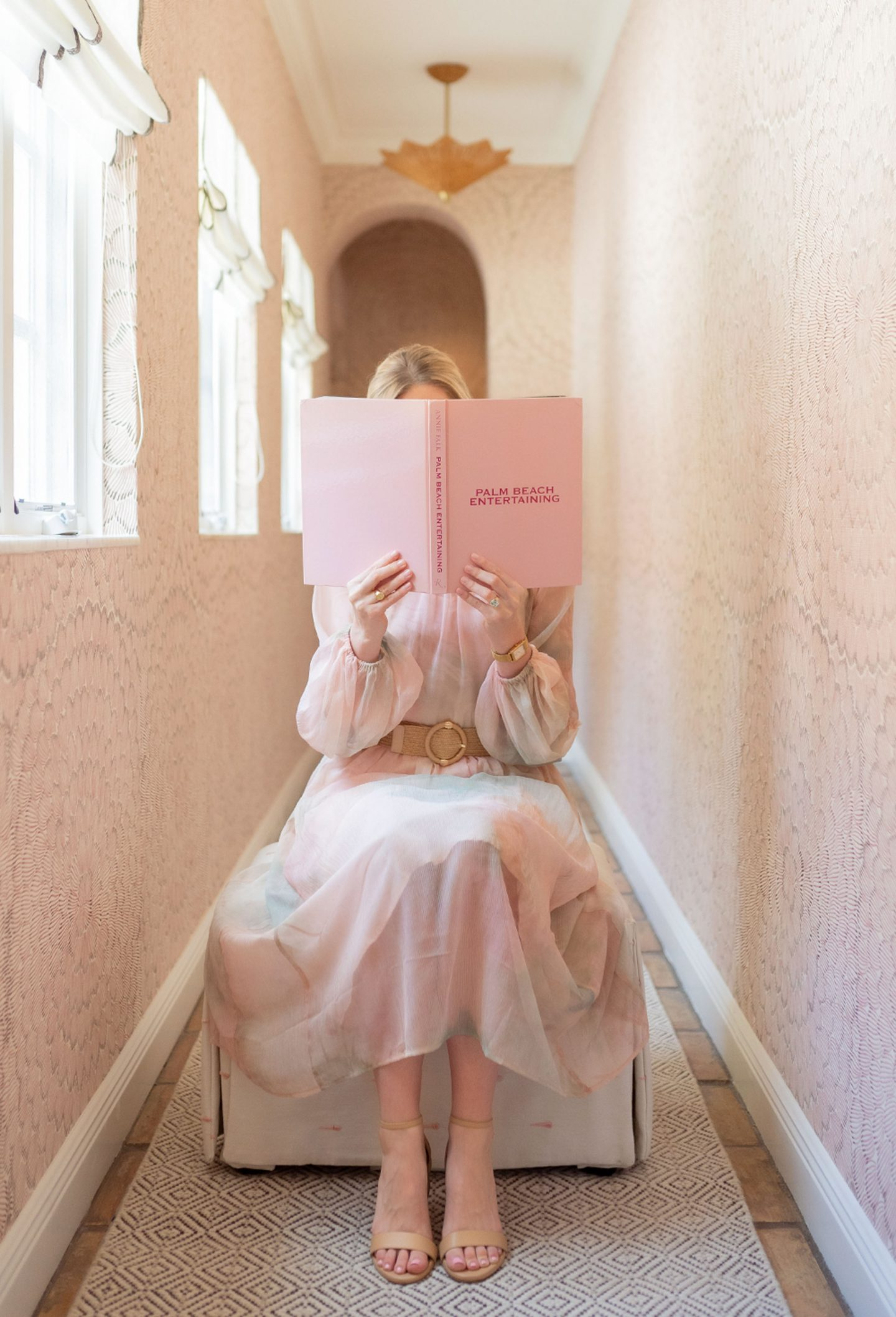 Ashley Brooke reading a book a pink hallway at The Colony Hotel in Palm Beach