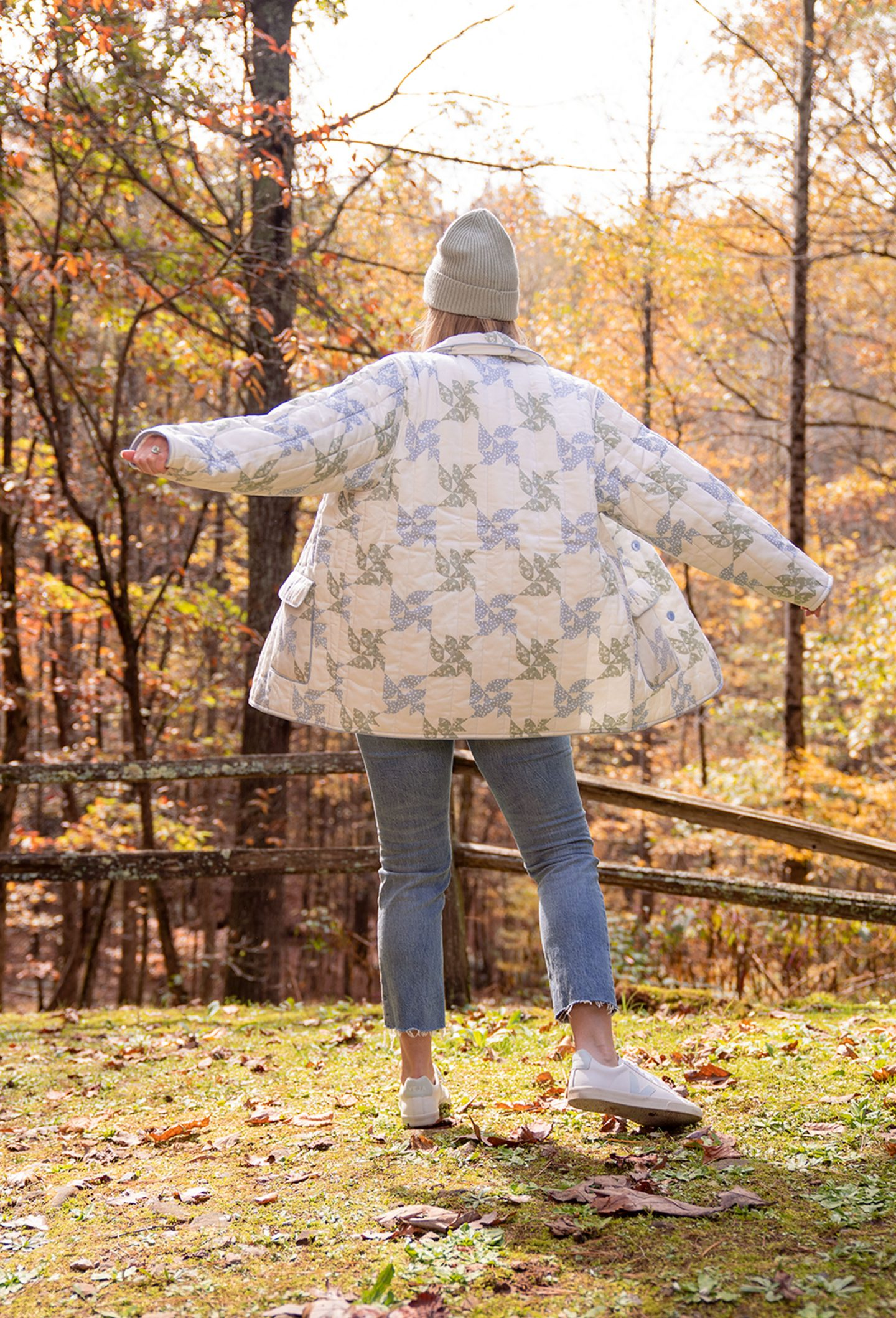Ashley Brooke twirling in quilted jacket outside her cabin